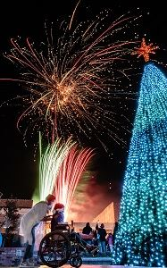 multicolored Christmas Tree, people all around, wheelchair kid looking at colorful fireworks